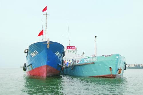 图为加油船正在紧张忙碌而又井然有序地为渔船加油.