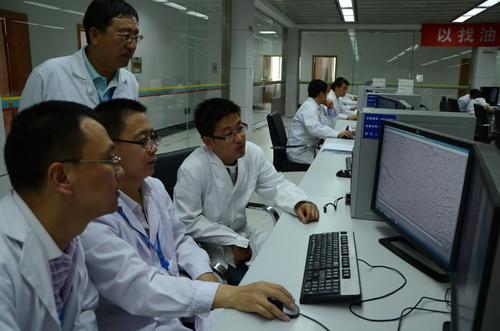 图为科技人员11月27日研究勘探剖面图.张冀 摄