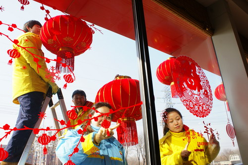 图为沈阳分公司金山路加油站员工欢天喜地挂起大红灯笼,贴上窗花